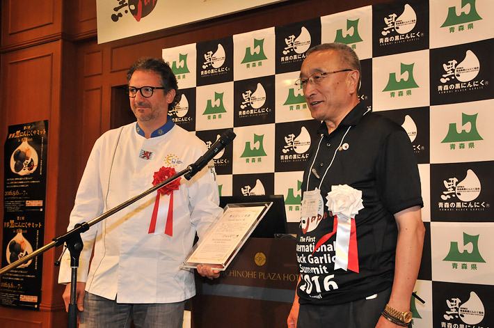 安倍首相の晩さん会を担当したルクセンブルクのシェフ(左)を「黒にんにく大使」に任命する柏崎理事長=9月6日、八戸市