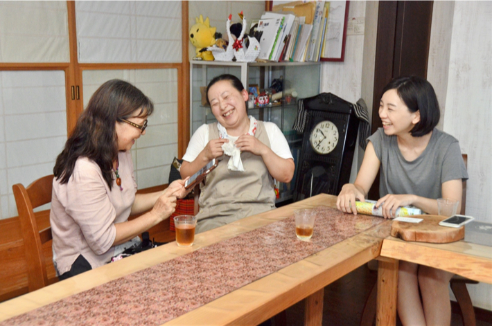 星雪館のリビングで台湾人宿泊客と談笑する門脇さん