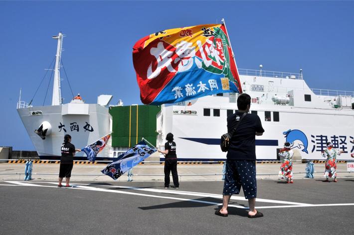 大間港に入港するフェリー「大函丸」を大漁旗で歓迎する町民