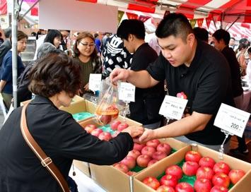 リンゴの販売では各県産の味を確かめようと、まとめ買いする客も多かった
