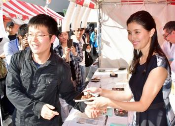 「東北和牛」のサイコロステーキ販売で、購入客との記念撮影に応じる橋本マナミさん(右)